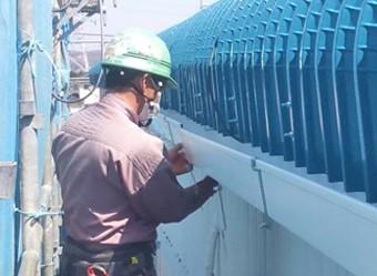 新しい金具と雨樋を設置している作業員